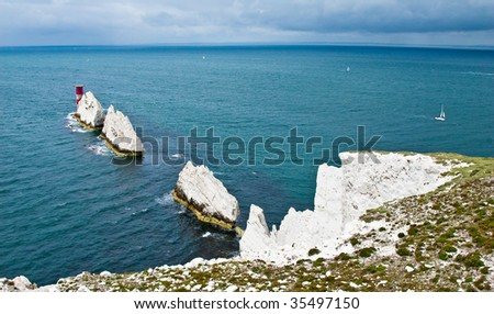 "The chalky rock formation called ""the Needles"" in located in Alum Bay (Isle of Wight, UK) with a red lighthouse and sailboat in the background."