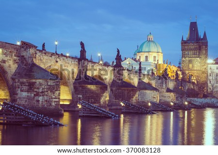 The Charles Bridge at night, (Czech: Karluv Most) is a famous historic bridge that crosses the Vltava river in Prague, Czech Republic. Vintage filter applied. - stock photo