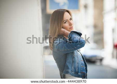 The  charming lady stands near ancient building