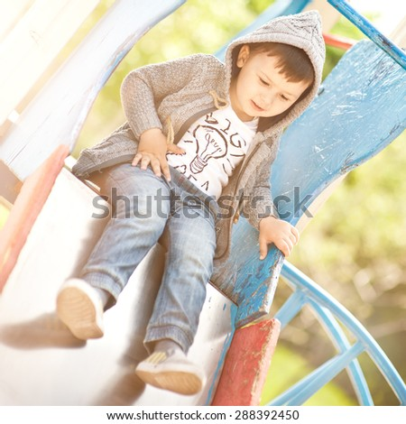 The charming little boy goes for a drive on a children's slide at the park