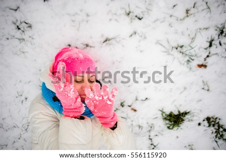 The charming young woman plays with someone in snowballs. She lies on snow and hides the face in hands. To the woman it is very cheerful. She is dressed in a bright ski suit.
