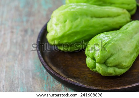 The chayote (Sechium edule) is a vegetable on wooden background - stock photo