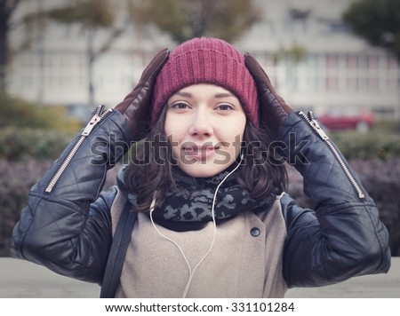 The cheerful beautiful girl in a leather jacket corrects red cap - stock photo
