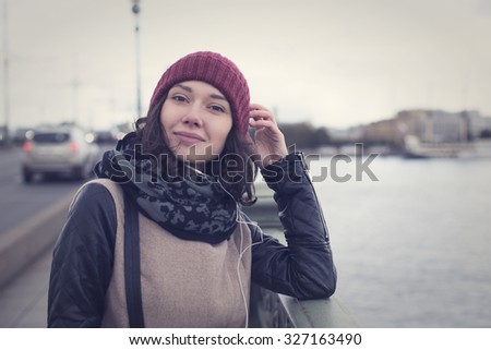 The cheerful beautiful girl in a leather jacket listening to music through white headphones on the Troitsky Bridge in Saint Petersburg - stock photo