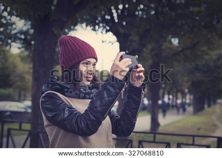 The cheerful beautiful girl in a red cap and a leather jacket photographed in nature on black telephone - stock photo