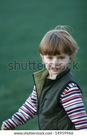 The cheerful kid on a green field of stadium