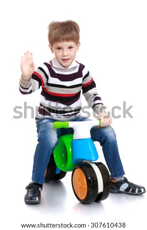 The cheerful little boy riding on a plastic two-wheeled bike. The boy waved his hand greeting someone-Isolated on white background - stock photo