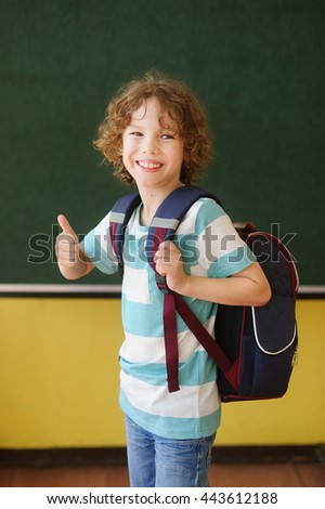 The cheerful pupil stands near a board in a class. He with a smile looks in the camera. Behind the back of the school student a backpack. Gesture of the boy shows that at it everything is all right.