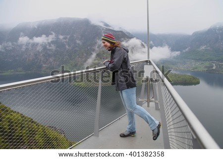 The cheerful young woman on an observation deck in mountains, Hallstatt Lake - stock photo