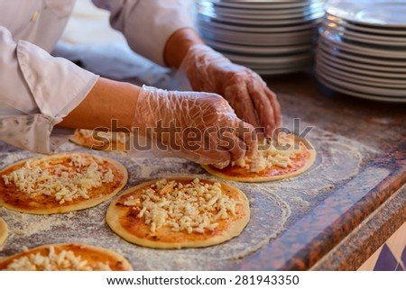The chef, who puts toppings on a pizza before baking - stock photo