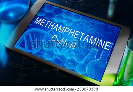 the chemical formula of Methamphetamine on a tablet with test tubes   - stock photo