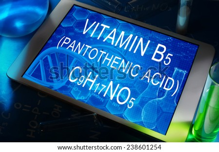 the chemical formula of Pantothenic acid (vitamin b5 or pantothenate) on a tablet with test tubes   - stock photo