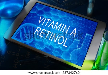 the chemical formula of Vitamin a (retinol) on a tablet with test tubes   - stock photo
