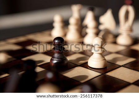 the chess pieces on a table in the park - stock photo