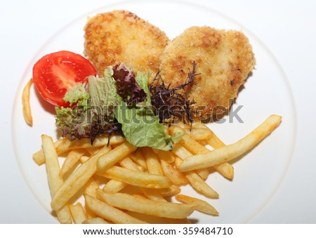 the chicken nuggets served with potatoes and greens - stock photo