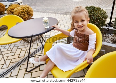 The child, a girl, baby, children sitting in cafes walking on sun summer street dressed in beautiful fashionable stylish dress, dear daughter cute kid, pretty face - stock photo