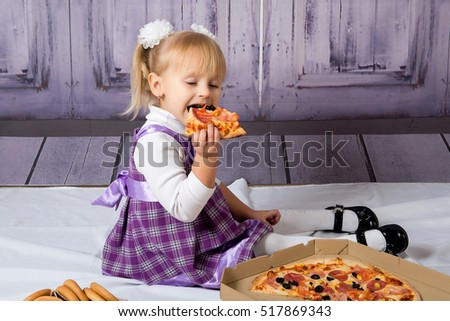 The child, a little girl sitting on the floor and having fun eating pizza. Unhealthy diets.