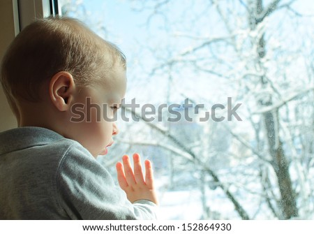 the child at a window - stock photo
