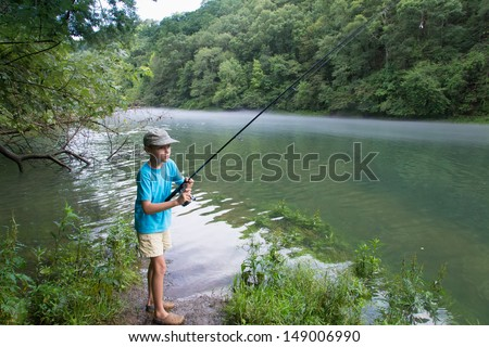 The child catches a fish in the river - stock photo