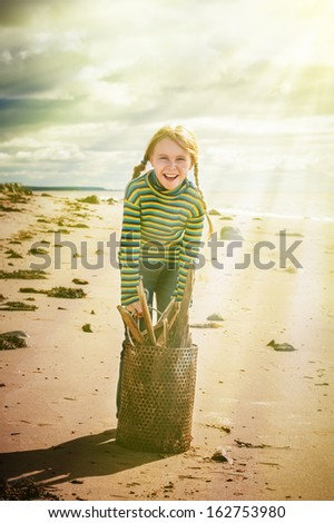 The child collecting trash in a bucket on the beach. - stock photo
