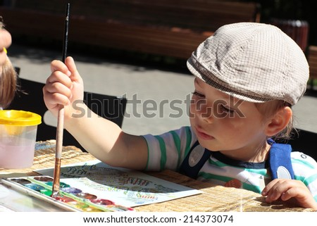 The child drawing with brush and watercolors - stock photo