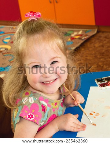 The child  draws and smiling, syndrome, down syndrome - stock photo