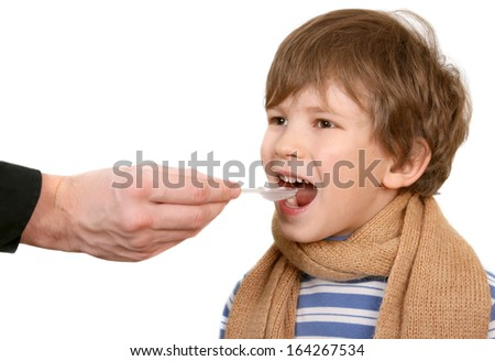 The child drinks a medicine from a spoon