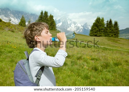 The child drinks water from plastic bottle in mountains - stock photo