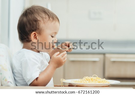 The child eagerly eats delicious pasta in the kitchen