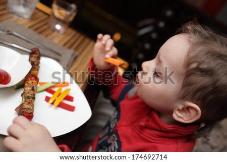 The child eating kebab at a cafe - stock photo