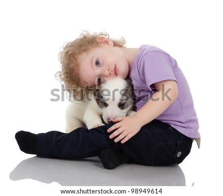 The child embraces a puppy dog. isolated on white background
