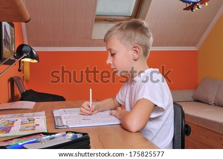 The child from primary school performs homework at his desk.