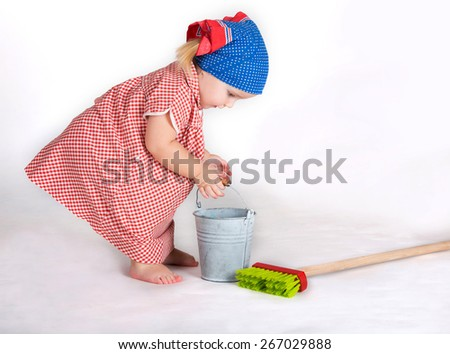 The child girl the housewife wearing red dotted cloth the cleaner with tools  - stock photo