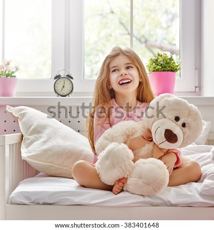 The child girl woke up and enjoys the morning sun.  - stock photo