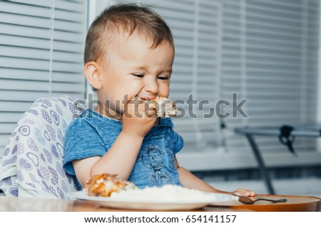 The child greedily eating chicken, fatty and delicious in the kitchen, very hungry