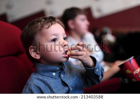 The child has popcorn in the cinema - stock photo