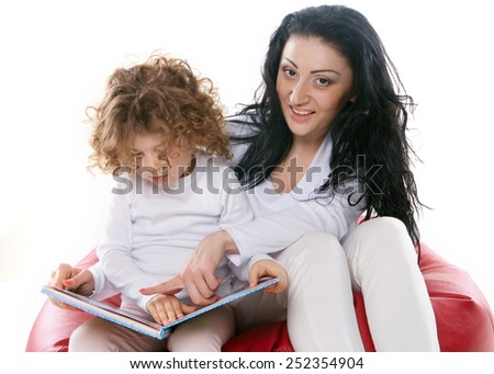 the child hold a book with mother isolated on the white background - stock photo