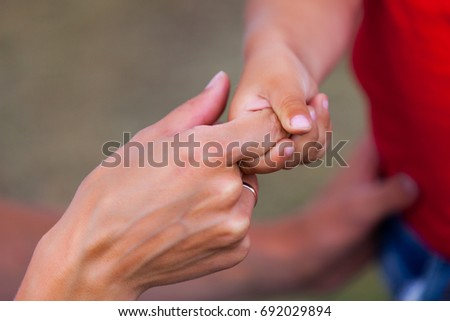 The child holds his mother's hand