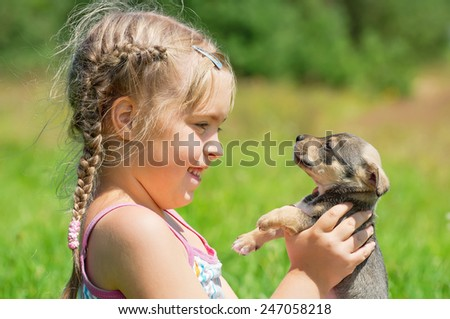 The child holds on hands of a little puppy - stock photo