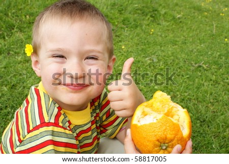 The child holds orange ,background grass