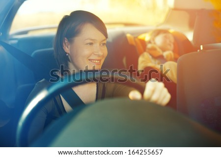 The child in a safety seat near to mother who sits on forward sitting of the car.