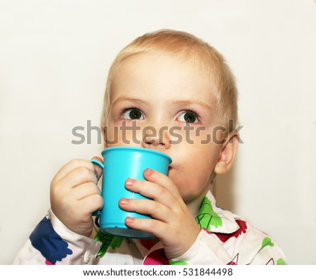 The child is drinking from a blue Cup