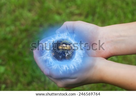 The child is holding a globe in his cupped hands.Green lawn in the background. Elements of this image furnished by NASA, - stock photo