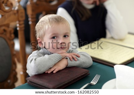 The child is sitting at a cafe - stock photo