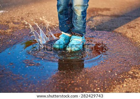 The child jumps in a puddle in sneakers