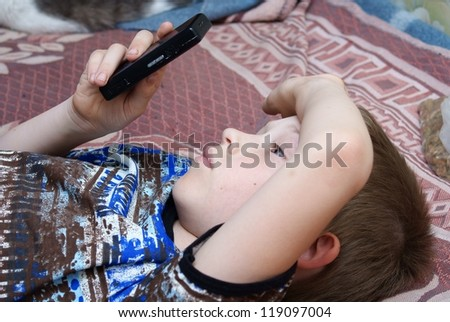 The child plays games on the mobile phone - stock photo