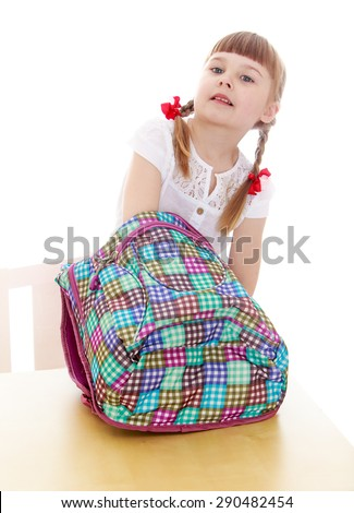 The child puts the book into his backpack ready for school - isolated on white background - stock photo
