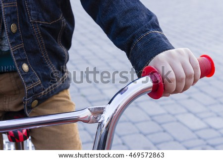 The child's hand to control the Bicycle handlebar. - Stock image. - Stock image