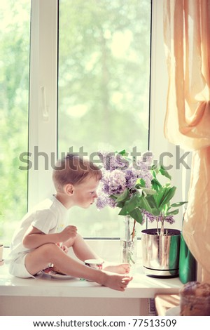 The child sits at a window - stock photo