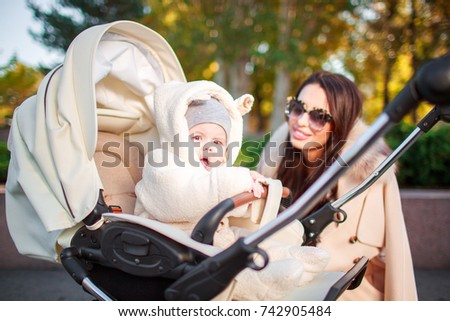 The child sits in a stroller and his mother looks at him. Outside.
